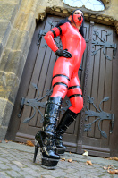 Sinful in pink latex and high boots in front of the church